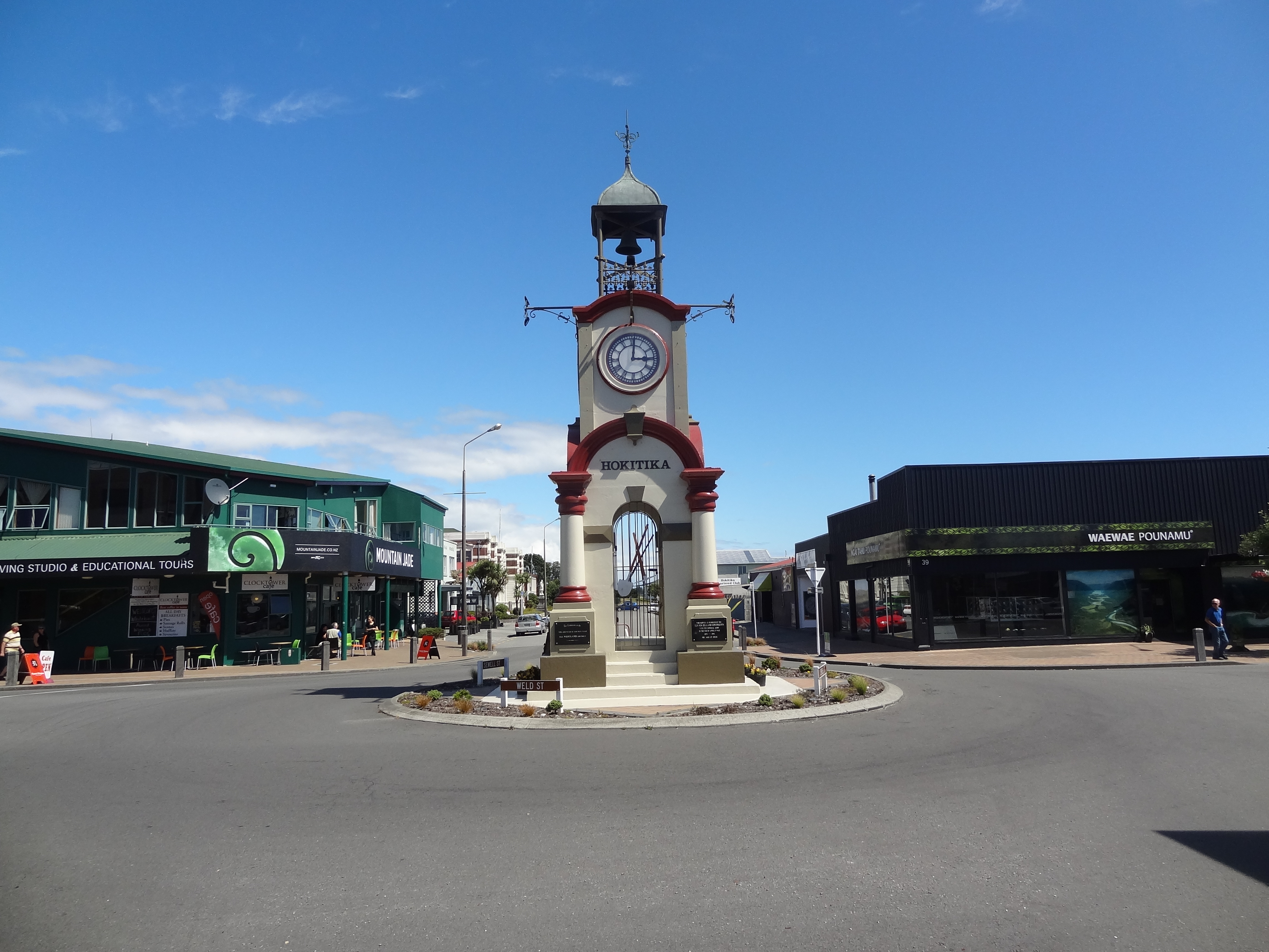 Hokitika Clock Tower.The first shops that can be seen on either side of the road are Pounami ( Greenstone ) Centres